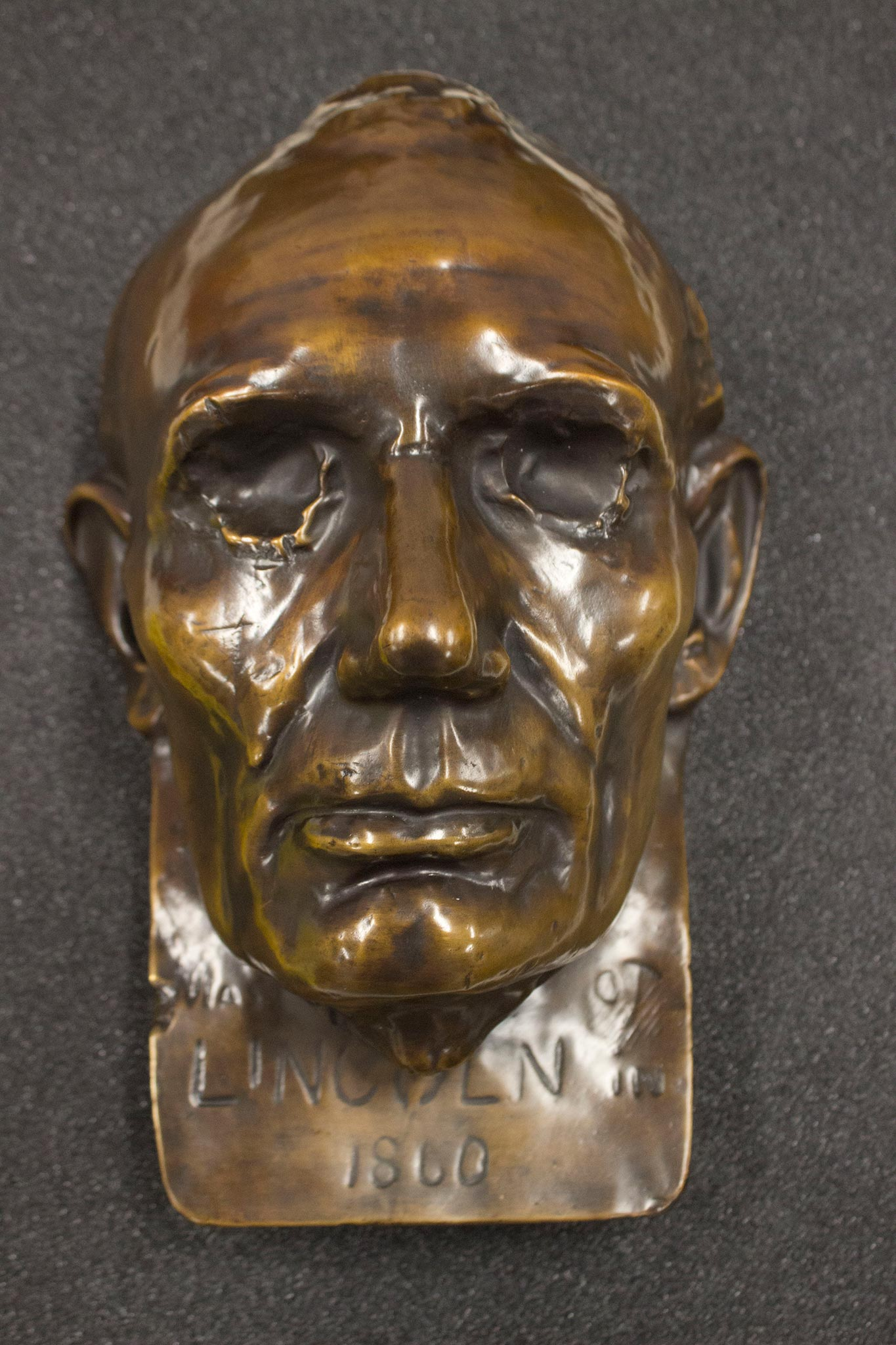 This is a bronze replica of the beardless life mask of Abraham Lincoln created by sculptor Leonard Volk in 1860. He created casts of Lincoln's hand as well. Volk used the face mask to create full busts of Lincoln, and other sculptors and artists have used this mask for their own work.